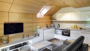 Nahoře vdřevěném podhledu je vidět kapsa, vníž jsou skryty reflektory. Všechen nábytek obývací části je vjedné výšce se sedákem kvalitní kožené sedačky tak, aby místnost působila opticky vyváženým dojmem.