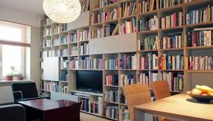 Jen uzavíratelné skříňky, zabudovaná televize a jídelní stůl narušily pravidelný čtvercový rastr knihovny plné knížek, které dávají prostoru život