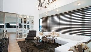 Obývací pokoj spojený s kuchyní je opticky rozdělený subtilní bílou policovou stěnou. Bílou koženou pohovku značky Knoll doplňuje ikonické křeslo Barcelona navržené slavným architektem. Mies van der Rohe jej navrhl už v roce 1929 a dnes jej vyrábí Knoll