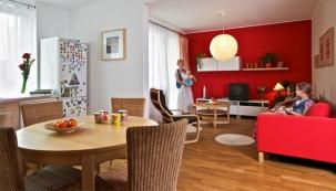 Červená stěna tvoří čelo hlavního obytného prostoru. Oproti přání majitelky, která původně chtěla červenou kuchyň, bude jednodušší barevný koncept kdykoliv změnit – stačí vymalovat