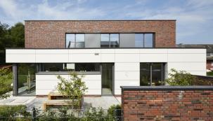 Dům v německém Rheine je domovem a kanceláříNa žádost klienta byly použity přírodní stavební materiály. Výsledná kombinace sestává z kabřincových cihel, fasády zvláknocementových desek a elegantních hliníkových profilů.