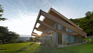 Architektonický výraz domu jednoduchého tvaru určuje  velký slunolam zlepených dřevěných hranolů, který jej zvenku obepíná ze tří světových stran. Stouto konstrukcí koresponduje přesahující střecha, obložená rovněž neupraveným modřínovým dřevem.