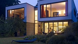 Projekt rodinného domu vychází zpožadavku klienta prostory co nejvíce otevřít směrem kjezeru. Nerušený výhled zprostředkovávají úzké okenní a fasádní profily Schüco.