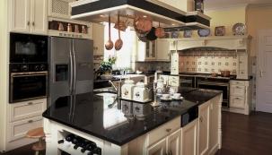 Část kuchyňské linky zhotovené vestylu Anglie Viktorian (Hš Rustikal) zmasivního dubu opatřeného krycí barvou vodstínu vanilla antik. Vespodní skříni jsou umístěné výsuvné zakázkové proutěné koše narámu. Horní aspodní skříňky spojuje drážkový panel spoličkou. Zprava vidíme detail římsy krbové vestavby aspodní skříňku varné části. Cena podle individuálních rozměrů od65000Kč, www.hsrustikal.cz