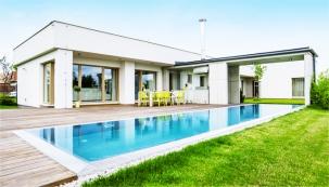 Všechny obytné místnosti jsou orientovány na dřevěnou terasu s velkým zapuštěným bazénem, v němž se zrcadlí střízlivá stavba nadčasového vzhledu.