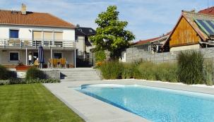 Dominantou zahrady je velký koupací bazén zasazený vtravnaté ploše, kolem něhož jsou umístěny dětské prvky.