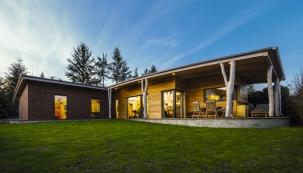 Osluněnou stranu domu lemuje dřevěná terasa, zčásti krytá přesahující střechou.