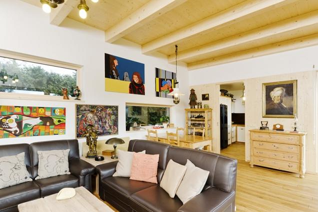 Podlaha zpřírodního dřeva astrop spřiznanými trámy asmrkovými prkny dávají interiéru mírně rustikální ráz. Obrazy korespondují shorizontálním oknem azvýšeným stropem.