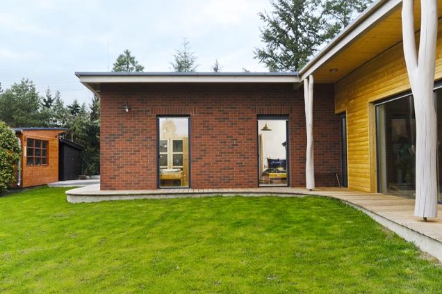Ložnicový trakt odlišuje obklad fasády zcihelných lepených pásků, společná obývací část domu je obložena neupraveným modřínem.