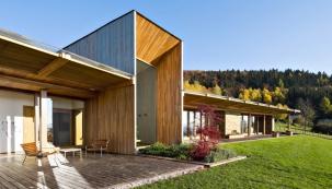 """Dům je rozdělen nadvě křídla, společnou obývací část aložnicovou část. Jejich """"svorníkem"""" je převýšená schodišťová hala, zvýrazněná zapuštěnou vertikální prosklenou plochou."""
