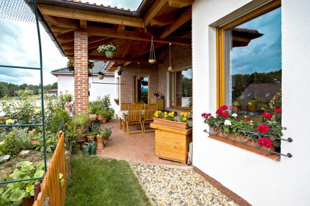 Pokud to počasí dovolí, může si rodina užívat díky posezení nazastřešené terase krásné prostředí zahrady. Vespodní partii okna si všimněte ručně kované dekorativní mřížky pro květinové truhlíky.