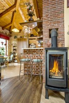 Krbová kamna pomáhají vzimě vydatně stopením. Přechod zhlavní obytné místnosti dokuchyně je naznačen proměnou povrchu podlahy aobloženým kuchyňským barem.
