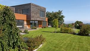 Architektonickou kompozici domu tvoří dva kvádry: přízemí je obestavěno přizdívkou  zrežných cihel aobsahuje společnou obývací část, ložnici rodičů azázemí, na něm je uloženo patro sdětskými pokoji, obložené neupraveným modřínovým dřevem.