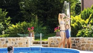 Solární sprcha Standard (výška 210 cm) má flexibilní sprchovací hlavici, zásobník na  35 litrů vody a mísicí baterii. V tomto případě se prezentuje jako stylový doplněk bazénů řady Azuro (MOUNTFIELD).