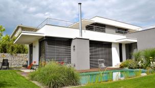 """Gabiony azelené střechy používá architekt Černý často jako architektonický atechnický prvek. Gabiony inafasády domů, protože je to přírodní materiál aizolant se zajímavou povrchovou strukturou. Přirozeně """"izolační"""" zelené střeše zase stačí pouze závlaha zdeště, jinak je bezúdržbová. Stejně jako nerezové zábradlí, které ji zároveň chrání i zdobí."""