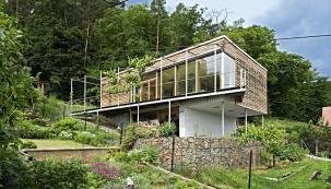 Dům se skládá zmasivní zděné základny, naníž je posazena lehká dřevostavba shlavním obytným prostorem aterasou. Tímto uspořádáním se vyřešilo problematické využití zahrady vprudkém svahu ipožadavek nahezký výhled dookolí.