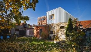 Východní pohled ze zahrady na dřevěnou přístavbu a plechovou nástavbu domu.