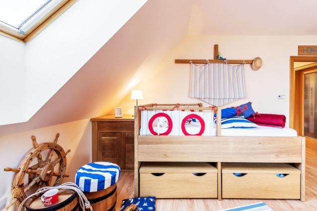Velká postel připomíná loď adokonce má iplachtu. Světlé atmavé tóny dřeva doplňuje červená, modrá abílá barva. Až se námořnický styl omrzí, stačí jen vyměnit dekorace.