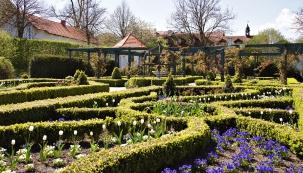 Ornamentální část zahrady sfontánou uprostřed. Stříhané ploty oživuje množství květin.