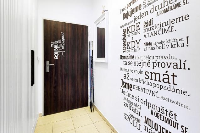 Výrazná tapeta zdobící stěnu vpředsíni má krátké pokračování inavchodových dveřích.