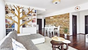 Výrazným prvkem interiéru je strom, který designérka vytvořila přímo vtruhlářské dílně, aobklad zpřírodního kamene procházející přes celou hlavní obytnou část odjídelního koutu až kestěně stelevizí.