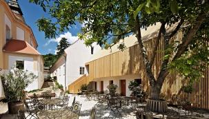 Původní inově postavené budovy obepínají dvůr, jemuž dominuje vzrostlý kaštan. Restaurovaná architektura je doplněna moderní dřevěnou stavbou.