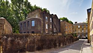 Řadu domů lemuje vysoká neprostupná zeď. Koncový dům má místo malého dvorku pěknou zahradu, dostatečně velkou pro umístění nové obytné přístavby.
