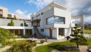"""Dominantu stavby představuje velké rohové okno vedruhém podlaží najihozápadním nároží, ještě zvýrazněné předsazenou hmotou obývacího pokoje. Jednolitá prosklená plocha bez rohového sloupku ajakéhokoliv členění poskytuje """"luxus"""" nerušeného výhledu nadaleký aširoký horizont, který si dům natomto místě plně zaslouží."""