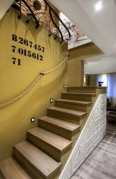 Zásuvky pod schodištěm slouží jako botník ajejich dekor je stejný jako ukuchyňské sestavy. Místo zábradlí majitel zvolil obyčejné lano. Sjeho upevněním pomáhal otec sdědou.