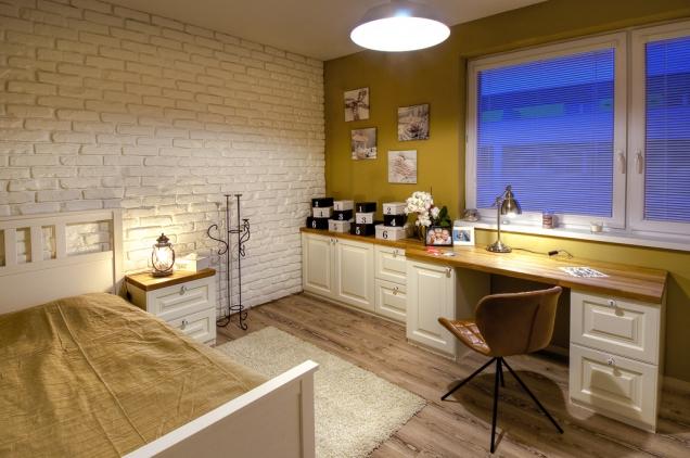 Cihlový obklad vdětském pokoji dostal bílý nátěr. Všechen nábytek kromě postele je vyroben namíru. Deska stolu je vyřezaná zjednoho kusu masivního dřeva.