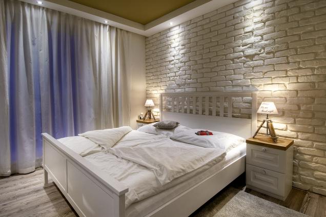 Barvy stěn vinteriéru jsou laděny dohněda nebo přiznávají přirozené odstíny cihel. Vložnici, kde je obklad přemalován nabílo, se hnědá pro změnu objevuje nastropě. Centrální světlo je nahrazeno náladovými bodovkami poobvodu místnosti.