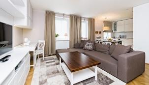 Obytný prostor sjídelnou akuchyní designérka přirozeně propojila pomocí jednotného stylu, pečlivě sladěných barev amateriálů. Dominantou pokoje je pohodlná  sedačka odfirmy Tom Tailor.