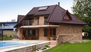 Pohled zjihu. Členitý tvar přízemí istřechy doplňují jednoduché prvky – moderní okna, nerezové zábradlí, ocelové sloupky nesoucí balkon.