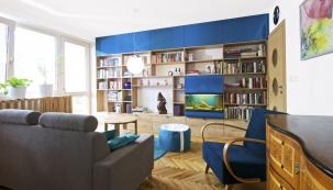 Prakticky řešený obývací pokoj je spojený skuchyní. Téma cestování amořských dálek prostupuje celým bytem aobjevuje se vpodobě kulatých výplní dveří nebo modrých tónů vinteriéru.