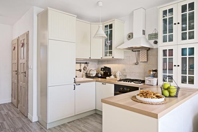 Smetanově bílá kuchyň zIKEA má jemně rustikální nádech ať už díky úchytům, decentnímu frézování dvířek, nebo zvoleným spotřebičům.