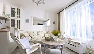 Dominantou obývacího pokoje je maximálně pohodlná obrovská pohovka skvětinovým vzorem koupená vKika. Doplňují ji subtilní bílé křeslo zIKEA azrenovovaný kulatý kávový stolek zbazaru.