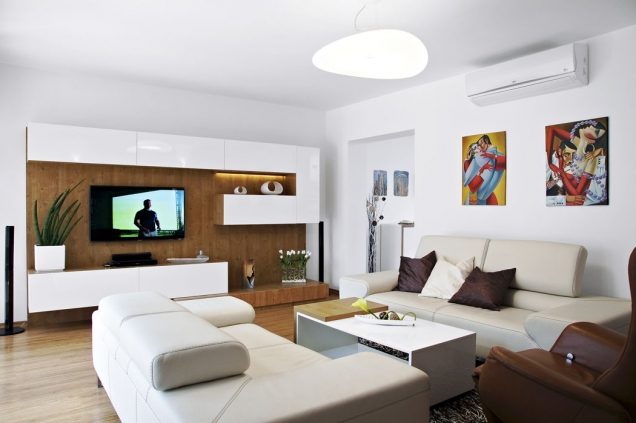 Podlaha vobývacím pokoji je pokryta vinylovou krytinou Termofix vdubovém dekoru, která odstínem koresponduje snábytkem zhotoveným nazakázku. Vpravo nahoře je zavěšen interní prvek dělené klimatizace.
