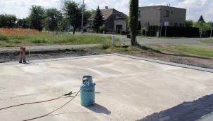 Navařování asfaltových izolačních pásů nazpenetrovanou základovou desku.