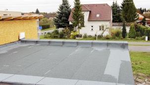 Střešní plášť je dokončený, povrch tvoří asfaltová hydroizolace se štěrkovým posypem. Na oplechování atik dojde až s fasádou.