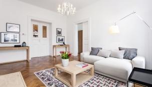 Dominantou obývacího pokoje je křišťálový lustr z30. let 20. století, který si majitelé koupili vobchodě se starožitnostmi vPštrossově ulici. Ostatní zařizovací prvky se pak drží jednouchých linií.