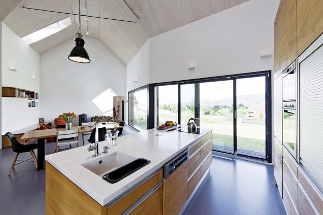 Panoramatické okno naplňuje interiér dojmy zvenku, vnitřní vybavení je proto jednoduché, vtlumených neutrálních barvách. Protiváhu podlahy zšedého marmolea tvoří dřevěné stropní desky sbílou lazurou.