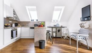 Kuchyň propojila designérka sobytným prostorem mimo jiné pomocí šedé úložné skříňky pod oknem, uníž stojí  židlička keklavíru, která je památkou naMartinovu babičku. Designérka jí dala nový nátěr.