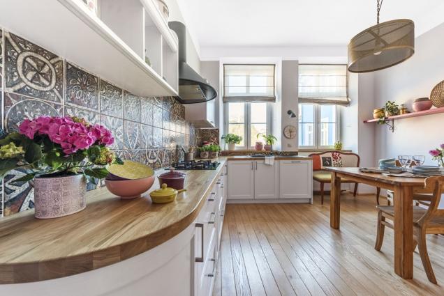 Centrální osvětlení kuchyně zajišťuje mosazný lustr (Snell Furniture), který designérka vmístnosti propojila smosaznými výplněmi růžové skříně.
