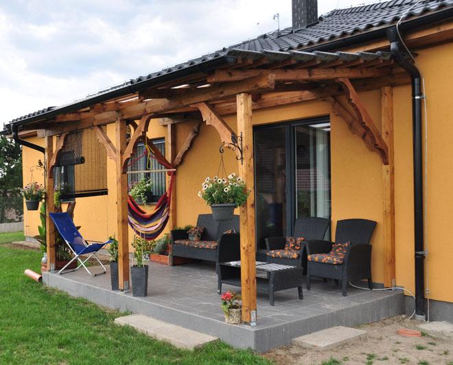 """Projekt č. 34: Terasa s průsvitnou střechou - Lukáš Bílek: """"Záměr byl jasný: k domečku postavit posezení – terasu. Jsem takový domácí kutil všeho druhu a baví mě práce se dřevem, a tak jsem se pustil do výstavby terasy sám vlastníma rukama. Nejprve jsem vybetonoval základy, pak mě čekalo položení dlažby, udělal jsem schody a nakonec to nejtěžší – stavba konstrukce terasy. Ohoblovat, naměřit, nařezat a nakonec natřít trámky. Chtěl jsem si ještě terasu zkrášlit, tak jsem si zkusil zdárně do vzpěr vyřezat ozdobu. …Položil jsem krytinu, na 1/3 střechy jsem použil prosvětlovací desky, abych nezastínil obývací pokoj, udělal jsem klempířinu (se kterou nemám žádné zkušenosti a trvala mi docela dlouho, ale nakonec se vše za pomocí přítele na telefonu povedlo) a terasa byla na světě!"""""""