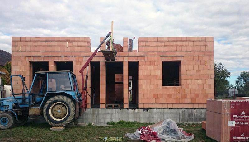 """Projekt č. 16: Rodinný dům vlastníma rukama - Michal Oleksulyn: """"...Na jedné fotce v příloze je takový zlepšovák. Místo """"vrátku"""" do patra jsem použil mnou vyrobený jeřáb za traktor a podlážku, na kterou přítelkyně naskládala cihly, synátor (6 let) v traktoru ovládal hydrauliku a já nahoře cihlu odebíral. No rodinná idyla na písku a maltě :)"""""""