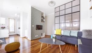 Kuchyň sobývacím pokojem propojuje jednolitý dřevěný dekor podlahy. Prostor zjemňují  odstíny zelenkavé tapety avýmalba vnejsvětlejším barevném tónu tapety a stejně tak decentní barevné odstíny sedacího nábytku akonferenčního stolku.
