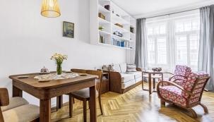 Jídelní stůl ažidle jsou další součástí původní výbavy. Samotný prostor je úžasně vzdušný aprosvětlený díky velkým oknům avysokým stropům, které jsou typické pro secesní domy.