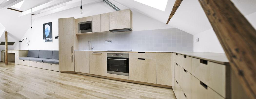 Nábytek je zhotovený zbřezové překližky, pracovní deska adřez jsou zbílého akrylátu. Natočení chladničky o20 stupňů je praktické pro práci vkuchyni azároveň nápadněji odděluje kuchyň odobývacího prostoru, který se tak zdá být větší.