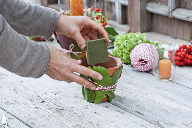 Aranžovací hmotu seřízneme pomocí nožíku tak, aby vyplnila celý květináč a zároveň zůstalo dostatek místa na vložení skleněného svícnu. Důležité je rovné seříznutí, aby svícen stál v květináči úplně rovně.