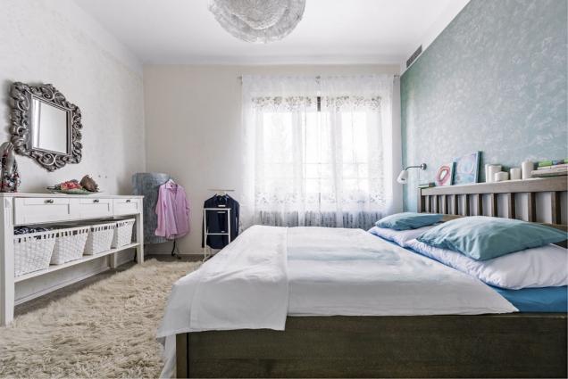 Ložnice je laděná douklidňujících tónů modré anadčasové bílé. Obrazy položené načele postele akrajkové svítidlo jsou opět Moničinými výtvory.